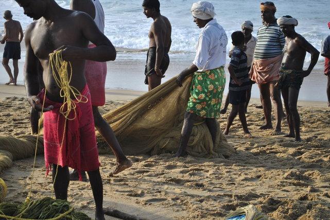 Dzieci kręcą się w pobliżu rybaków z Kerali zarówno przed wypłynięciem w morze, jak i po powrocie. Czasem tylko przeszkadzają przy składaniu sieci. Morze Arabskie, Kovalam, Indie.•Foto:. D. Jaworska