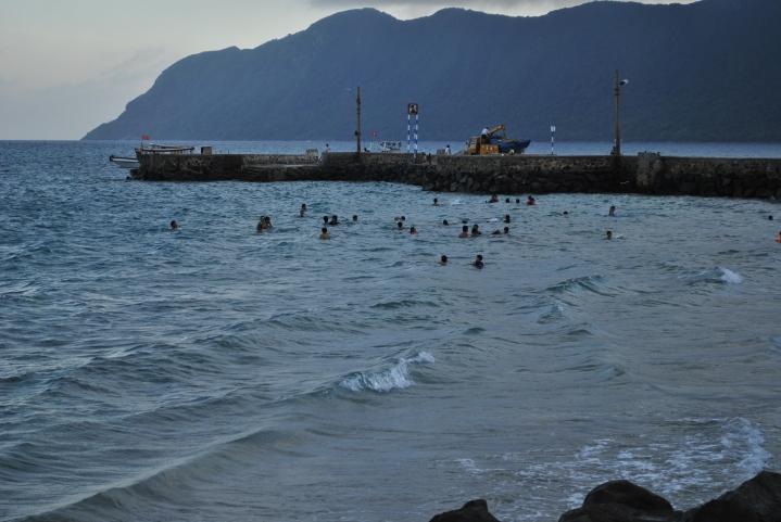 Mieszkańcy Con Dao co wieczór spotykają się w wodzie przy brzegu. Nie pływają. Moczą się i słuchaja wieczornych wiadoności nadawanych przez szczekaczki we wsi.. Foto: D. Jaworska